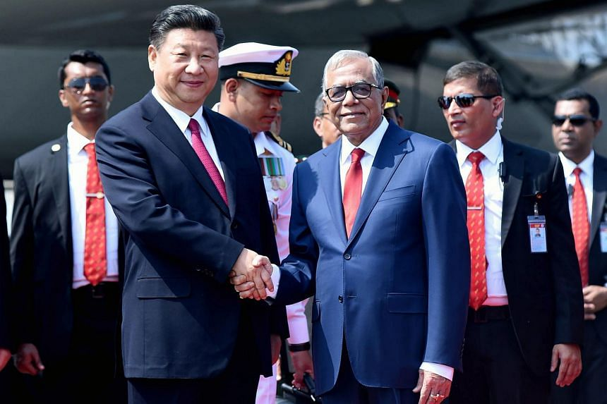 Chinese President Xi Jinping (left) is greeted by Bangladesh's President Abdul Hamid after arriving in Dhaka on Oct 14, 2016.