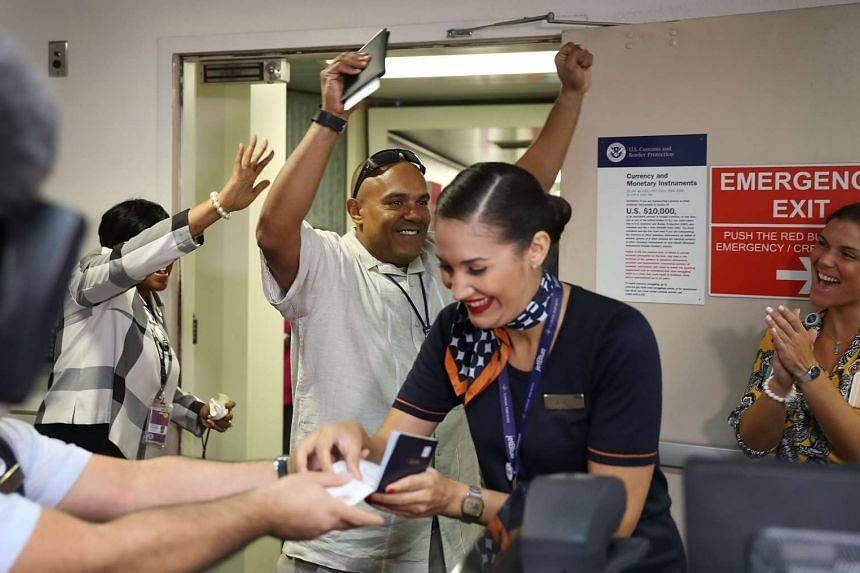 Angie Mueses (centre) checks passengers in as a happy traveler behind her celebrates before he walks down the ramp to JetBlue Flight 387 the first scheduled commercial flight to Cuba since 1961 on Aug 31, 2016 in Fort Lauderdale, Florida.
