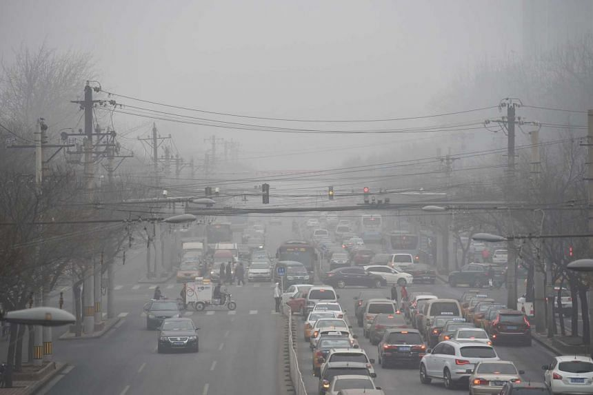 Cars driving below a blanket of smog on a heavily polluted day in Beijing.