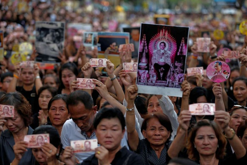 People hold Thai baht notes and portraits of Thailand's late King Bhumibol Adulyadej as they wait on the roadside while his body is moved from Siriraj hospital, to the Grand Palace, in Bangkok.