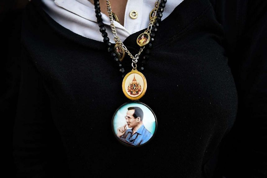 Pendants bearing the image of the late Thai King Bhumibol Adulyadej is worn by a mourner outside of the Grand Palace in Bangkok.