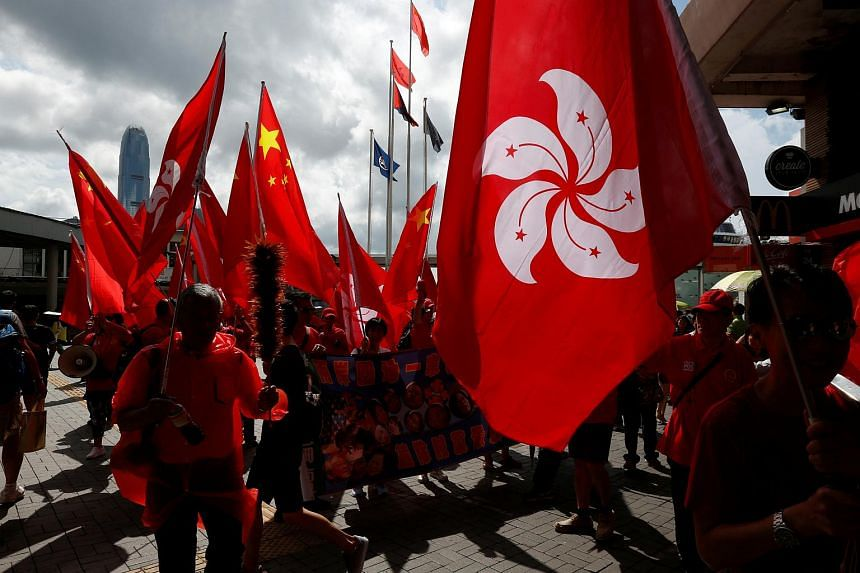 Pro-China supporters carrying a Hong Kong flag and China's national flags march at Tsim Sha Tsui shopping district to celebrate China's National Day in Hong Kong on Oct 1, 2016.