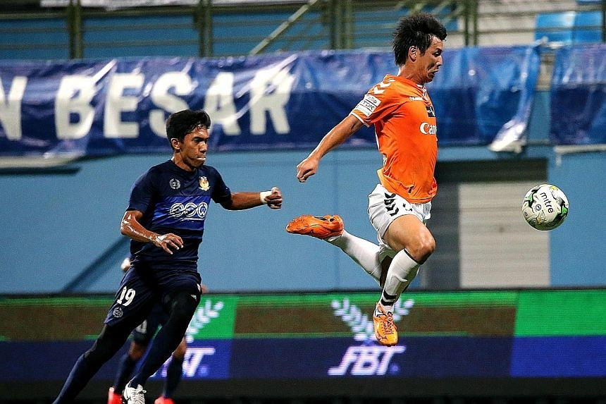 Atsushi Kawata lunging for the ball, as Hougang defender Nurhilmi Jasni races to keep up with him. Kawata opened the account for Albirex in the fourth minute with his 13th goal of the season.