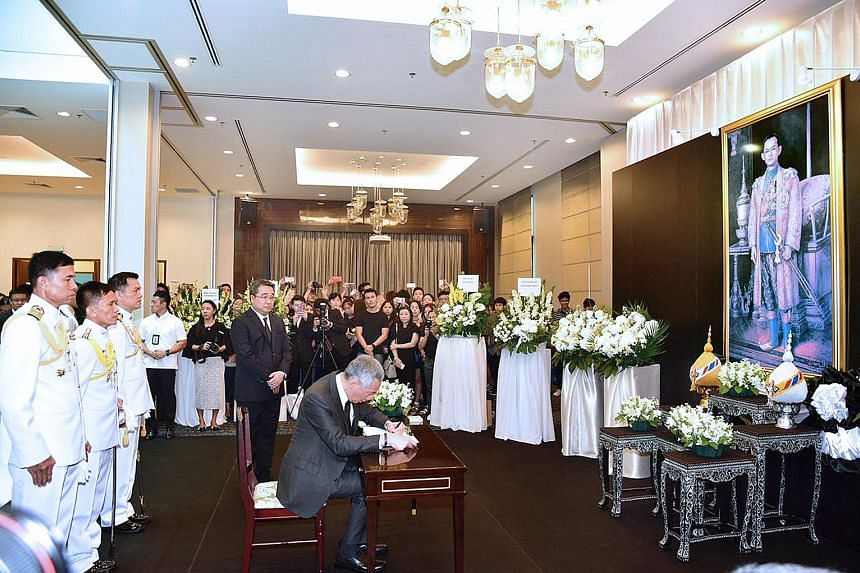 PM Lee signing the condolence book for the late King Bhumibol at the Royal Thai Embassy in Singapore yesterday. He wrote: ''His Majesty worked tirelessly for the people of Thailand throughout his long reign, and brought great progress to his country.