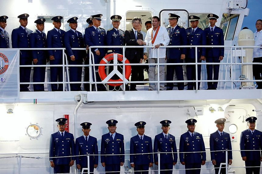 Mr Duterte (in white) on a newly built Philippine Coast Guard vessel. Analysts believe that the President's upcoming state visit to China will be a chance for both sides to discuss ways to dial down tensions in the South China Sea.