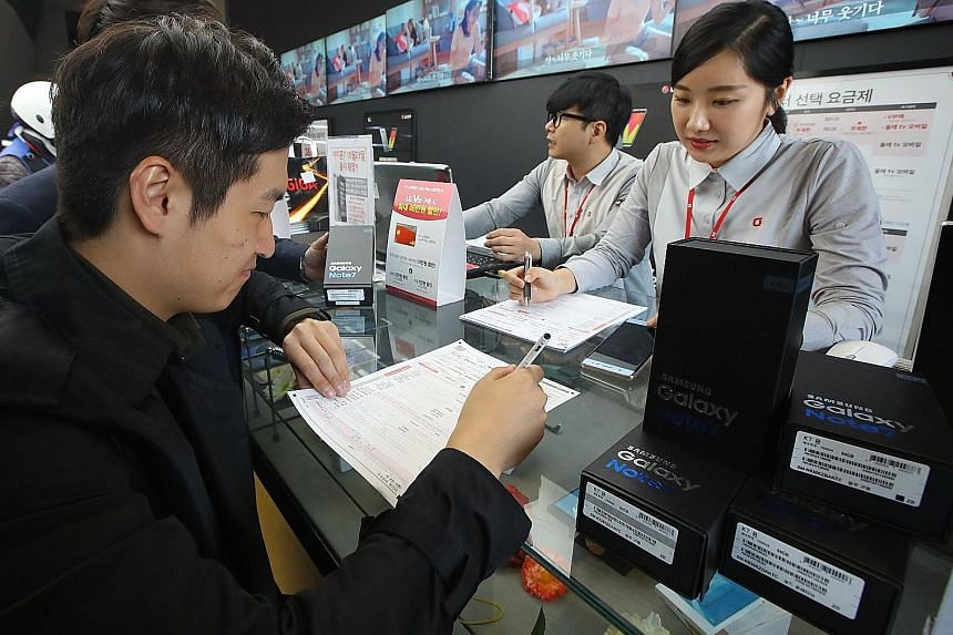 Customers returning their Samsung Note7 mobile phones at a dealership in Seoul yesterday. Samsung shares have slumped more than 8 per cent this week, wiping about US$20 billion (S$28 billion) from their market value.