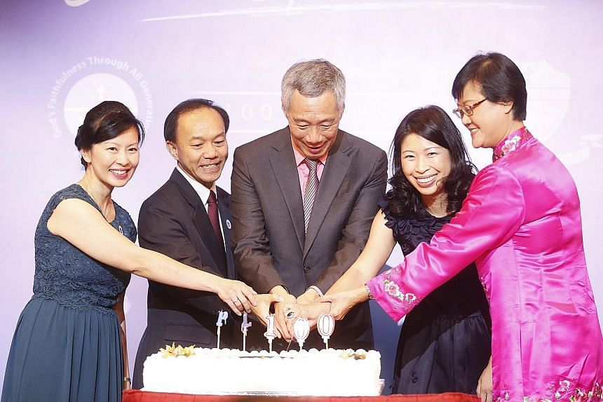 PM Lee cutting a cake last night at the Orchard Hotel ballroom with (from left) Mrs Quek Li Gek, principal of PLMGS (Secondary); Professor Hum Sin Hoon, chairman of the Board of Management; Mrs Quahe-Lim Su-Lynn, president of the alumni; and Ms Chua