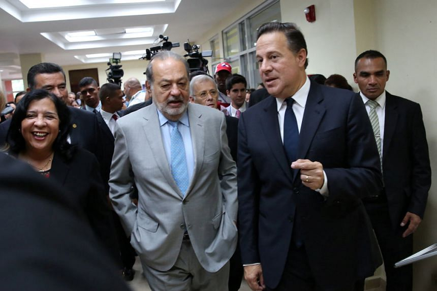 Carlos Slim (centre) speaks with Panama President Juan Carlos Varela (right) at an event in Panama City, on July 22, 2016.