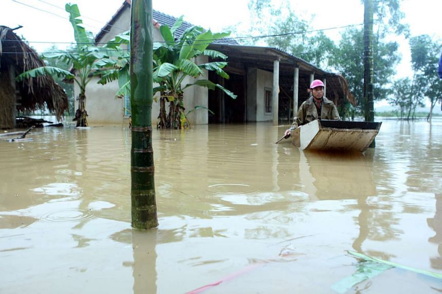 A man paddles a boat near his submerged house during a flood in Vietnam's central Ha Tinh province, Oct 15, 2016.