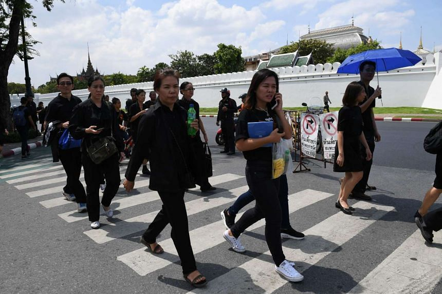 Thai people wanting to get a glimpse of the funeral caravan carrying Thai King Bhumibol Adulyadej, wear black clothes as they approach the vicinity of the Royal Palace in Bangkok.