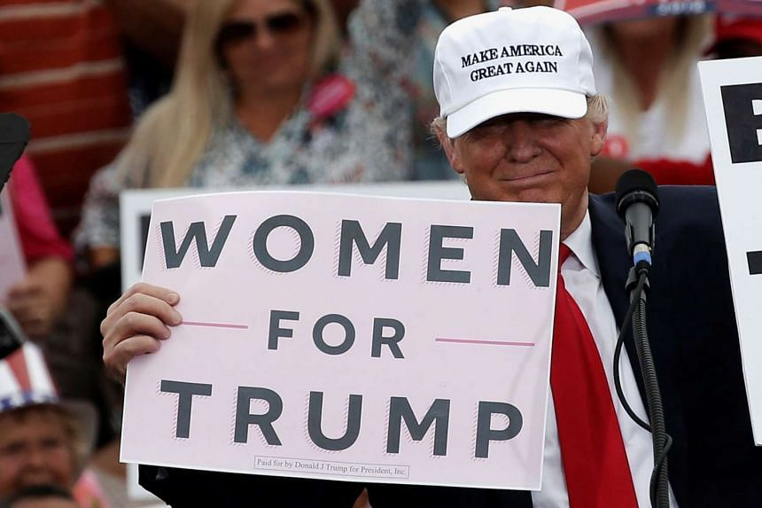 Trump holds up signs at the end of a campaign rally in Lakeland, Florida, Oct 12, 2016.