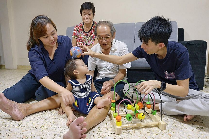 Mrs Stephanie Tan, her husband Sean, and his parents Tan Kim Hok, 76, and Madam Oh Pang Huck, 71, having a good time with 15-month-old Sarah in her grandparents' flat in Ang Mo Kio. The young couple have been shuttling between their parents' places w