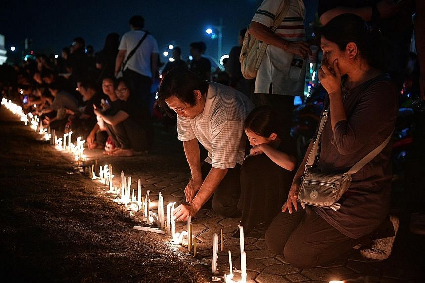 Mourners praying as they light candles during a vigil for Thai King Bhumibol Adulyadej outside the walls of the Wat Phra Kaew, or the Temple of the Emerald Buddha, which is located within the grounds of the Grand Palace, yesterday.