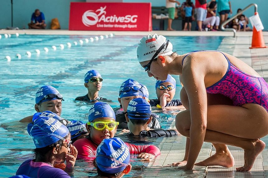Team Singapore swimmer Amanda Lim (right) took time off her training schedule yesterday afternoon to speak to participants at a swim clinic held ahead of the Oct 21-22 Fina/airweave Swimming World Cup. Lim and fellow national swimmers Danny Yeo and L
