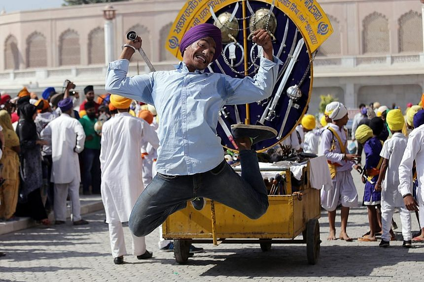 A young Sikh displaying his skill with a sword while demonstrating gatka, an ancient Sikh martial art, during a religious procession in Amritsar, India, yesterday. It was the eve of the 482nd birth anniversary of the fourth Guru or master of the Sikh