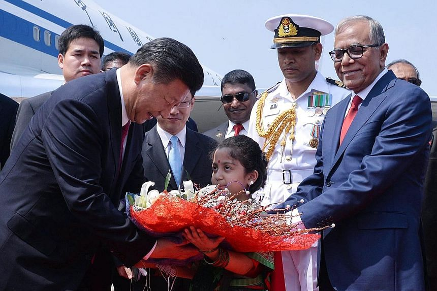 Mr Xi being greeted by Bangladeshi President Abdul Hamid upon his arrival in Dhaka.