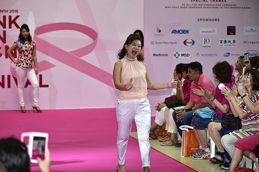 Ms Lily Chan, 53, gives the thumbs up to her friends and supporters as she walks down the catwalk. The crowd responds with cheers for the breast cancer survivor, who was first diagnosed with the condition in 2010. 	She was joined by other breast canc