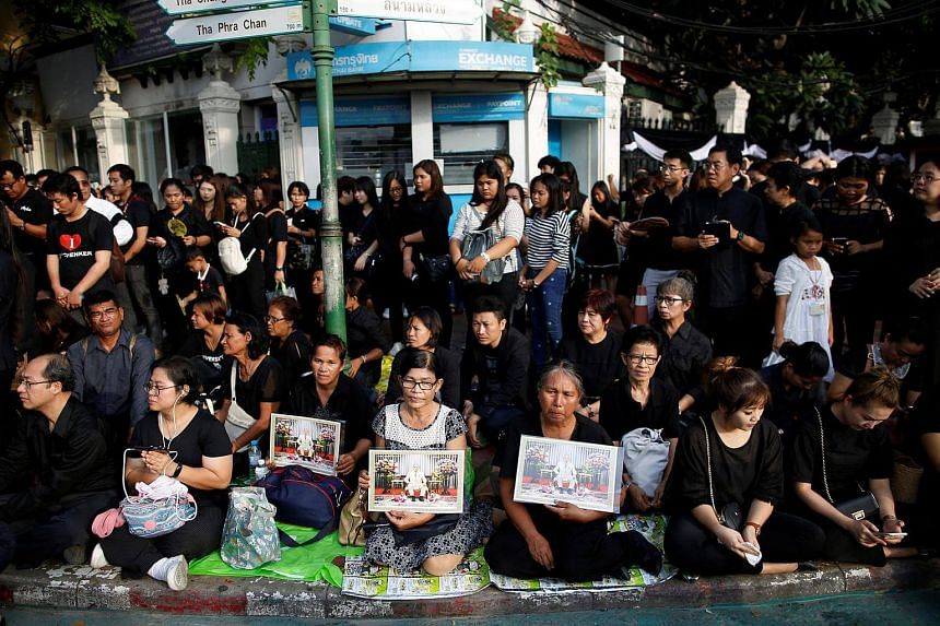 People sit on a street as they offer condolences for Thailand's late King Bhumibol Adulyadej in front of the Grand Palace in Bangkok on Oct 15, 2016.