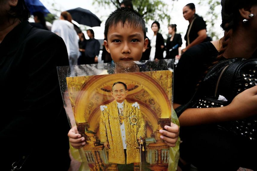A boy carries a portrait of late Thai King Bhumibol Adulyadej while waiting to pay his respects at the Grand Palace in Bangkok on Oct 16, 2016