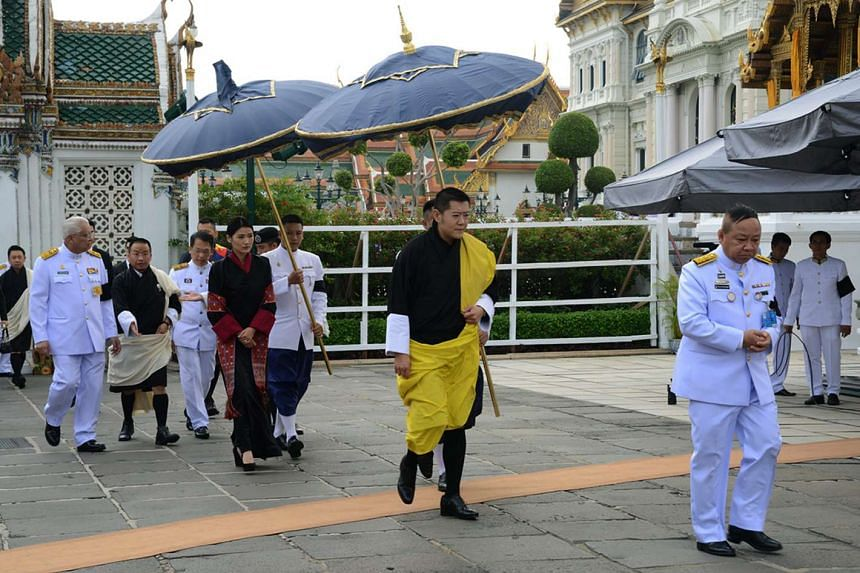 Bhutanese King Jigme Khesar Namgyel Wangchuck (centre) and his wife Jetsun Pema arriving to pay their respects to the late Thai King Bhumibol Adulyadej, in Bangkok on Oct 16, 2016.