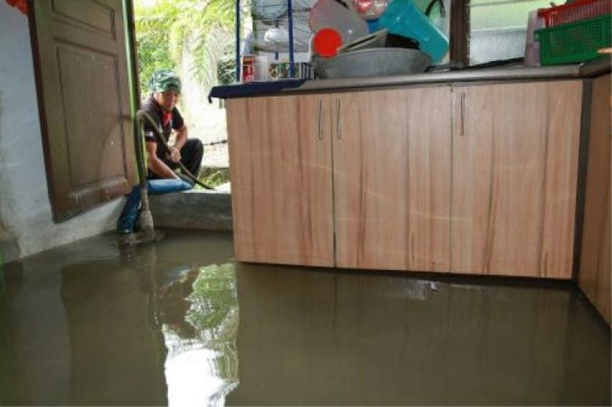A villager pumping water out from the kitchen after it was flooded during the high tide at Batu 5, Kampung Sementa, Klang.