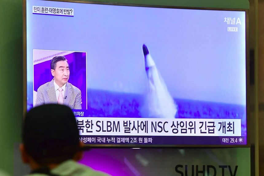 A man watches TV news showing file footage of a North Korean missile launch on Aug 24, 2016.