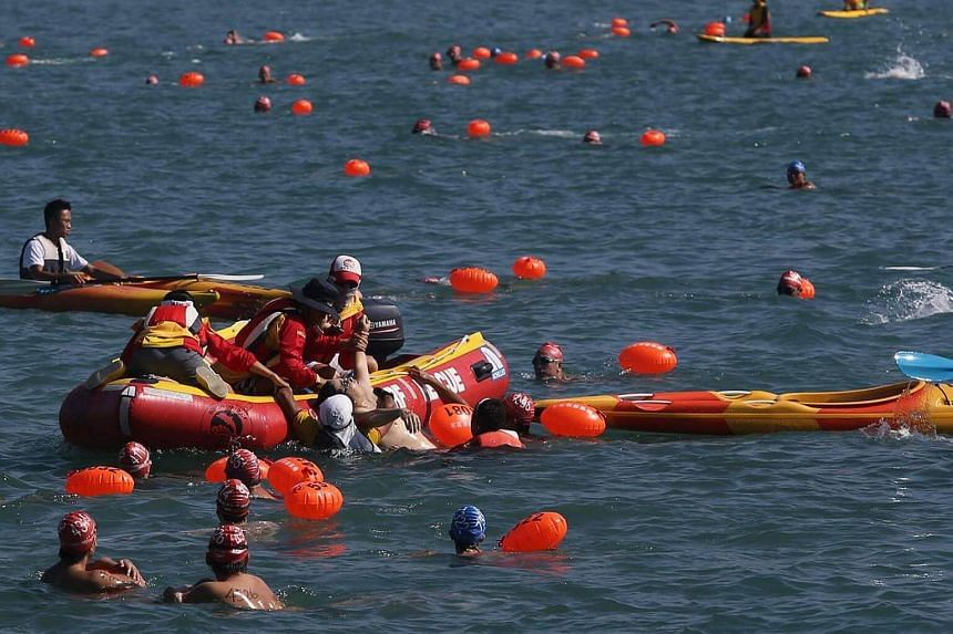 Rescuers pull out of the water a swimmer who drowned during the annual Harbour Race in Hong Kong on Oct 15, 2016.