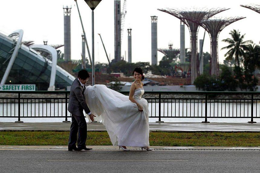 A couple taking their wedding photos along the Marina Promenade.