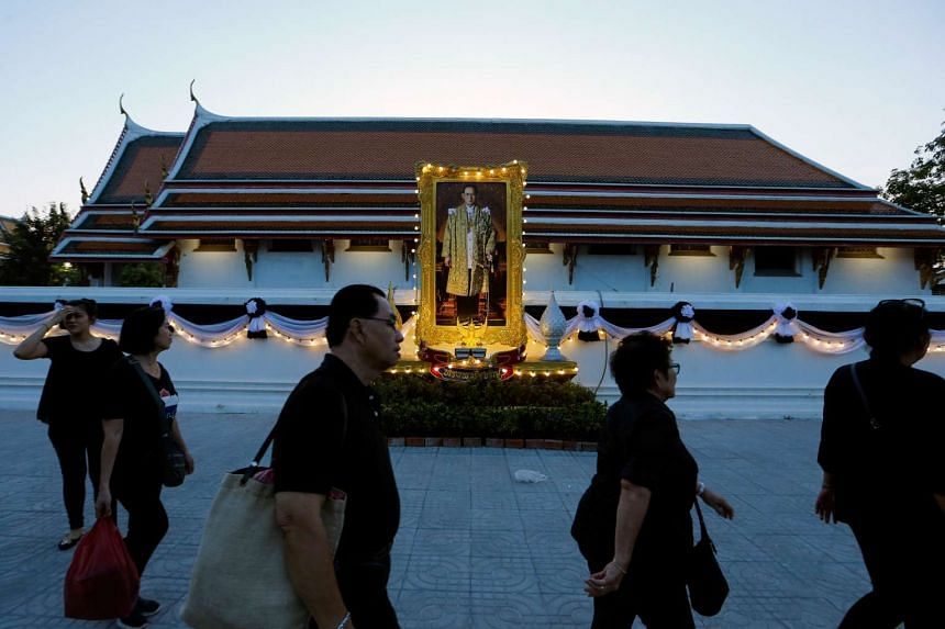 Mourners walks past a portrait of Thailand's late King Bhumibol Adulyadej in front of the Wat Pho temple in Bangkok, Thailand on Oct 15, 2016.