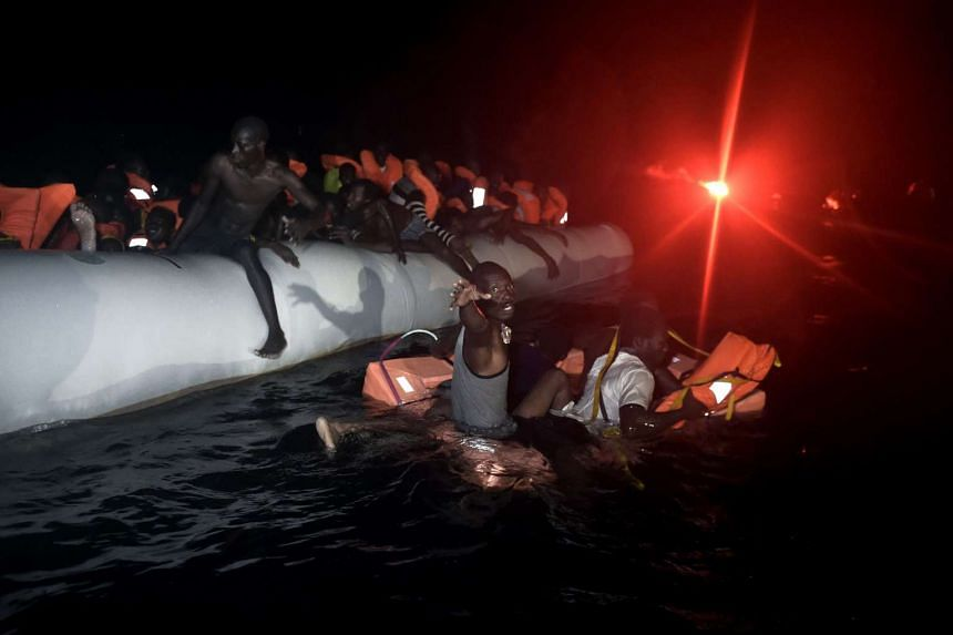 Migrants and refugees wait to be rescued from their sinking rubber boat some eight nautical miles off Libya's Mediterranean coastline on Oct 12, 2016.