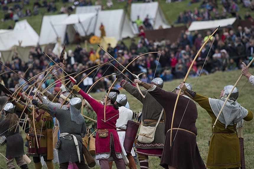"""Clad in mediaeval garb and chain mail, aficionados of the Middle Ages gathered in East Sussex in southern England on Saturday to re-enact the Battle of Hastings, 950 years later. At the site of the pivotal event, a thousand """"soldiers"""" representing th"""