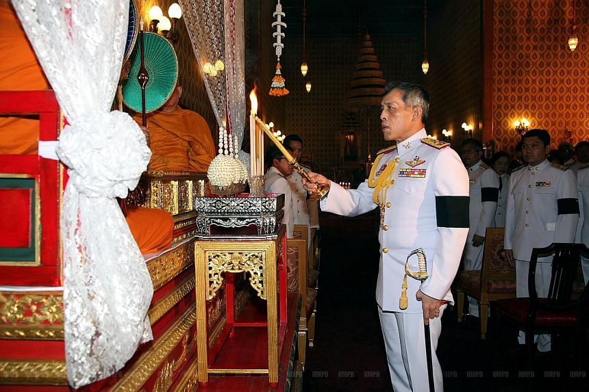 Thai Crown Prince Maha Vajiralongkorn lighting a candle in a ceremony honouring King Bhumibol at the Grand Palace in Bangkok on Saturday. A mourner praying as others queued to pay respects to King Bhumibol at the Grand Palace yesterday. Some Thais ha