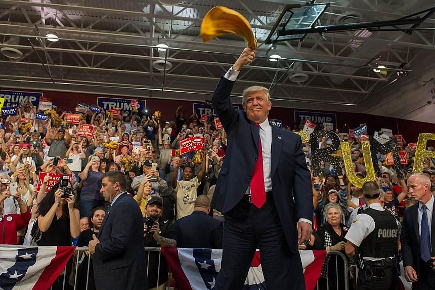 Mr Trump waving a Pittsburgh Steelers rally towel in front of his supporters in Ambridge in Pennsylvania, where he received a rousing welcome from thousands. A queue outside the Ambridge Area High School last Monday stretched for half a kilometre. Mr