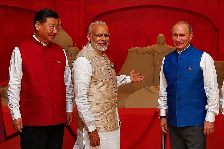 (From left) Mr Xi and Mr Modi with Russian President Vladimir Putin at the eighth annual Brics summit on Saturday. Brics leaders issued a joint declaration on a range of measures, including the setting up of a new credit ratings agency.