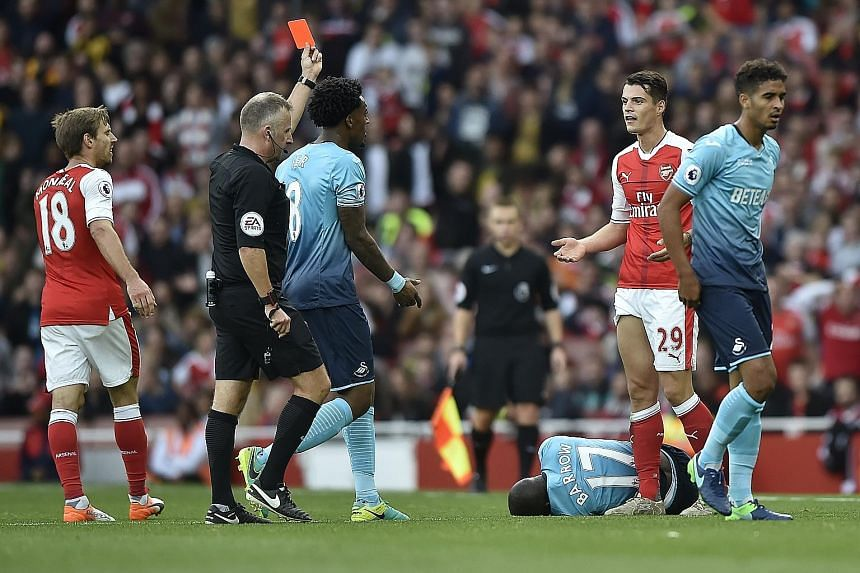"""Referee Jonathan Moss giving Arsenal midfielder Granit Xhaka (No. 29) a red card for a tackle on Modou Barrow (lying prone on the ground) during the 3-2 win over Swansea City on Saturday. Arsenal manager Arsene Wenger said of his midfielder: """"He is n"""