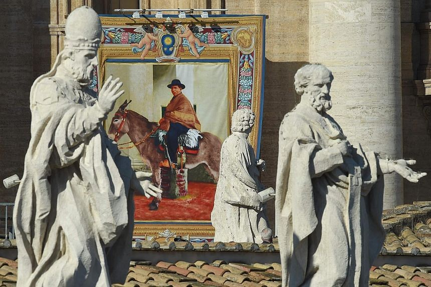 A tapestry portrait of new saint Jose Gabriel del Rosario Brochero hanging from the facade of St Peter's Basilica during a canonisation mass led by Pope Francis yesterday.
