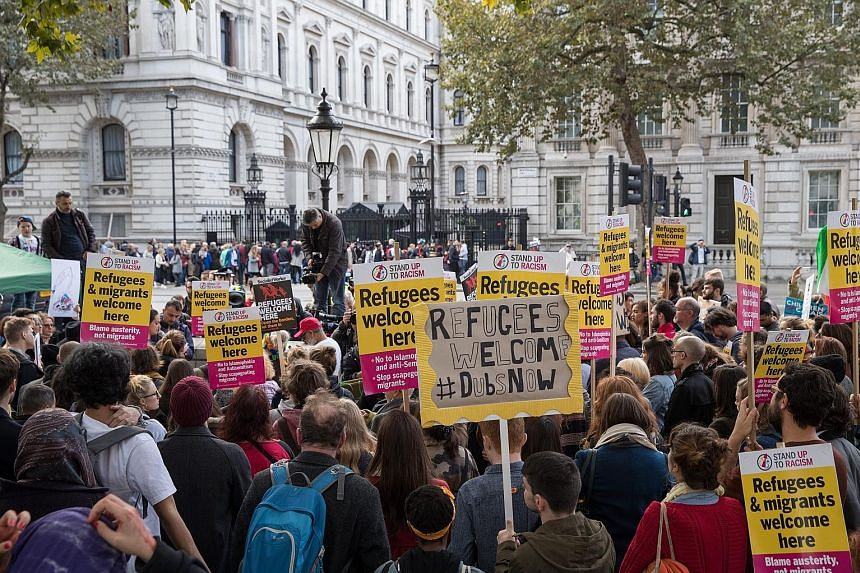 Demonstrators at Richmond Terrace in front of Downing Street, London, on Saturday, condemning the inhumane treatment of refugees and demolition of camps, particularly at Calais in France.