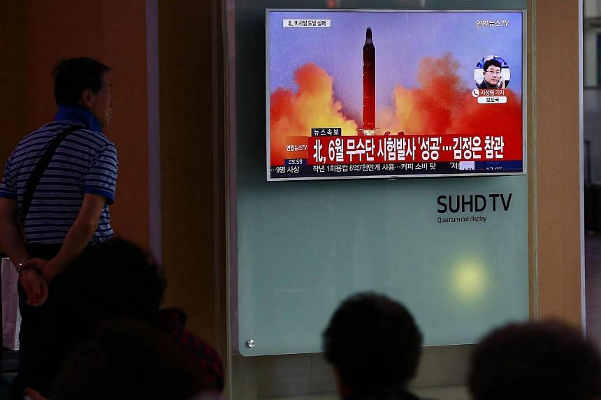 South Koreans watch a television news broadcast at a station in Seoul, South Korea on Oct 16, 2016.