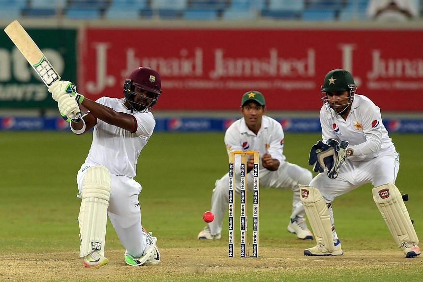 West Indies batsman Darren Bravo (left) hits a shot as Pakistani wicketkeeper Sarfraz Ahmed (right) looks on during the fourth day of the first day-night Test between Pakistan and the West Indies at the Dubai International Cricket Stadium in the Gulf