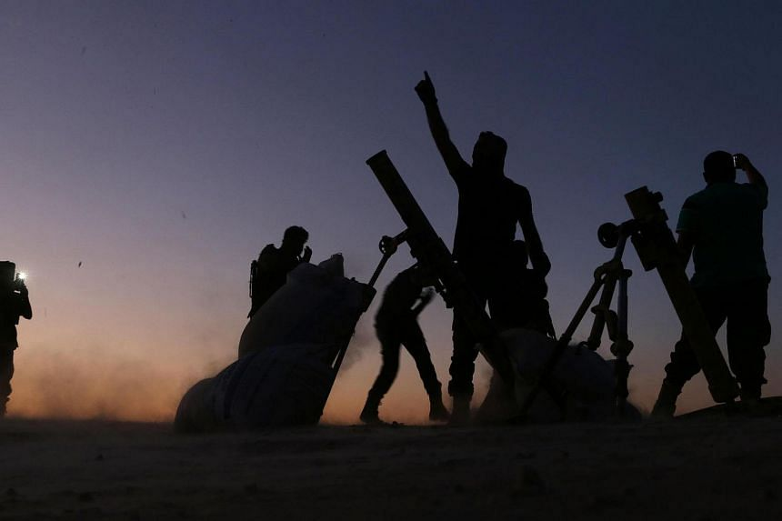 Fighters from the Free Syrian Army cheer and react as they fight against the Islamic State (IS) group jihadists on the outskirts of the northern Syrian town of Dabiq, on Oct 15, 2016.