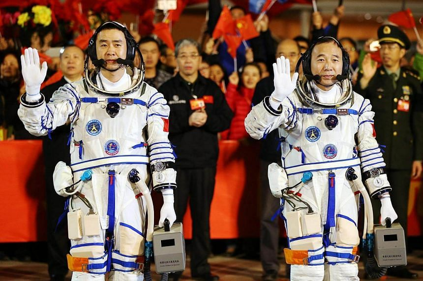 Chinese astronauts Jin Haipeng (right) and Chen Dong wave during a farewell ceremony before embarking for the launch of the Shenzhou-11 spacecraft at the Jiuquan Satellite Launch Center in Jiuquan in Gansu province, China, on Oct 17, 2016.