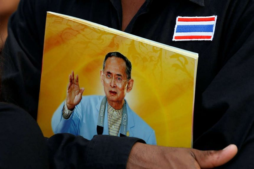 A mourner holds a portrait of the late Thai King Bhumibol Adulyadej while waiting to pay respects to him, outside the Grand Palace in Bangkok, on Oct 17, 2016.