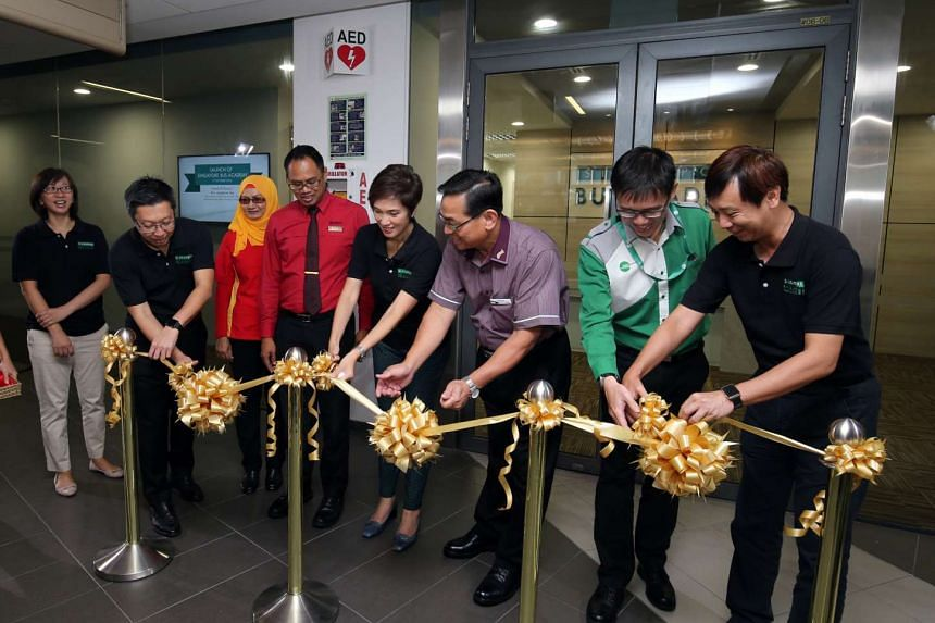 Senior Minister of State for Transport Josephine Teo (fourth from right) helps cut the ribbon at the launch of the new Singapore Bus Academy.