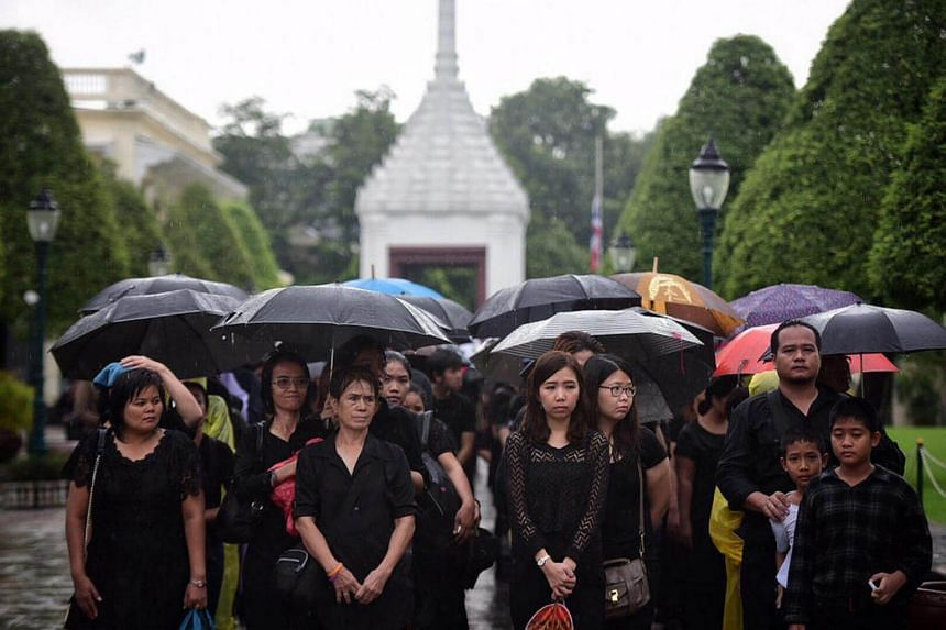 Mourners wait to sign a condolence book inside Bangkok's Grand Palace.