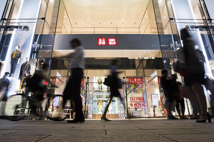 Pedestrians walk past the exterior of a Uniqlo store, operated by Fast Retailing Co., at night in the Ginza district of Tokyo, Japan.