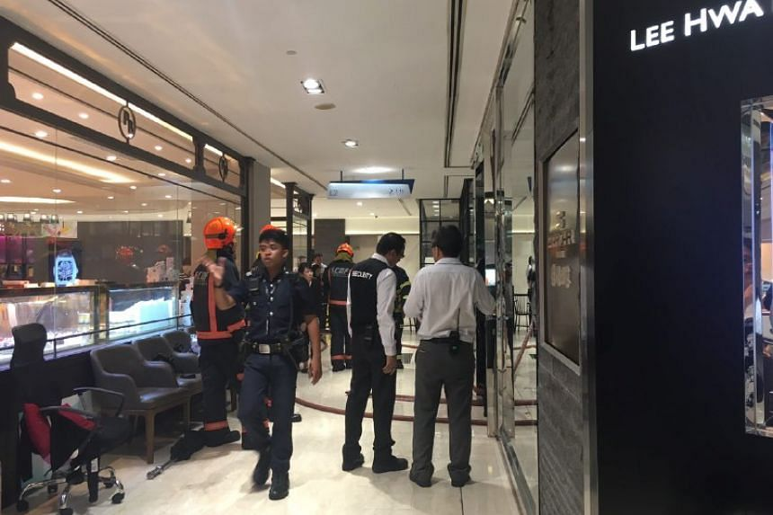 Staff cleaning the area in Wisma Atria after a fire on Oct 17, 2016.