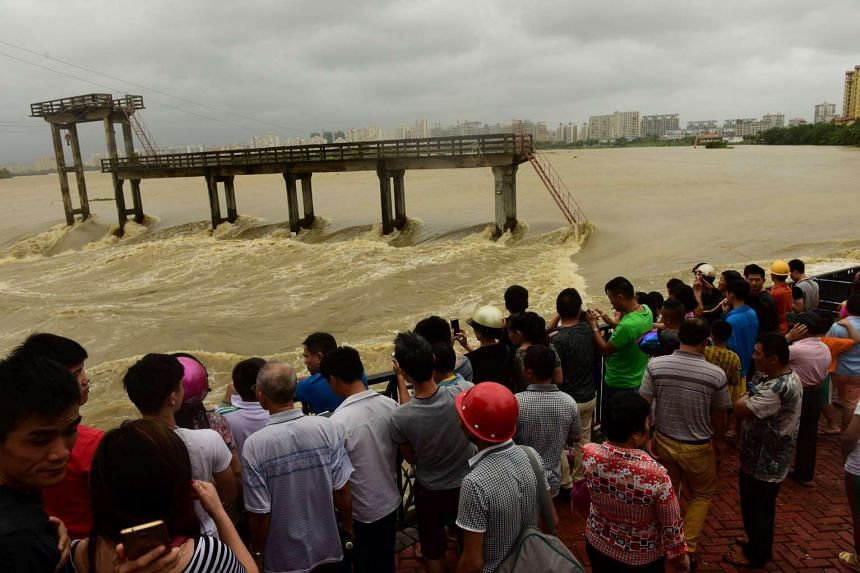 People stand near a flooded river after Typhoon Sarika hit Qionghai, Hainan province, on Oct 18, 2016.