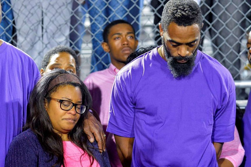 Shoshana Boyd and Olympic sprinter Tyson Gay stand surrounded by family and friends during a candlelight vigil for their daughter on Oct 17, 2016.