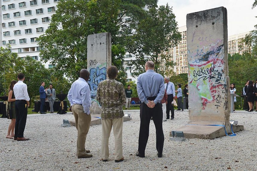 Invited guests look at the two slabs of concrete that used to be part of the Berlin Wall, now installed in the National University of Singapore.