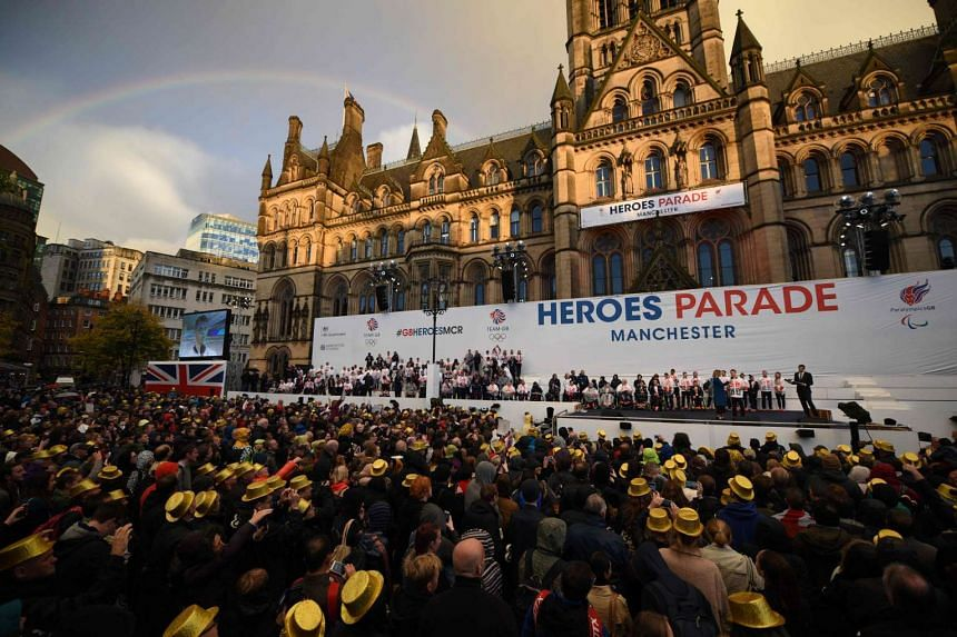 "A rainbow appears in the sky as members of the British Olympic and Paralympic teams are applauded by the general public on a stage in front of Manchester Town Hall after taking part in a ""Heroes' Parade"" through the streets of Manchester in north wes"